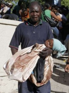 A injured haitian man carries his dead daughter