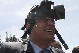 With a gas mask on his head, Ecuador's President Rafael Correa gestures as he runs away from tear gas during a protest of police officers and soldiers against a new law that cuts their benefits at a police base in Quito, Ecuador, Thursday. Mr. Correa tried to speak with a group of police protesters but was shouted down.