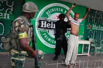 The Americas Post - Jamaican soldiers frisk for weapons at a checkpoint.  Photo credit:  AP