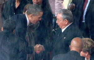 President Barack Obama (L) greets Cuban President Raul Castro during the official memorial service for former South African President Nelson Mandela at FNB Stadium December 10, 2013 in Johannesburg, South Africa. President Obama announced the U.S. will re-establish its diplomatic relations with Cuba, and open economic and travel ties between the two nations after a decades-long embargo. (Photo Credit : Getty)